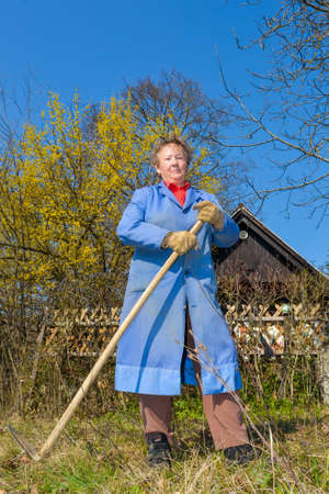 house coat: Elderly woman in blue coat posing in front of a house with hoe in her hands