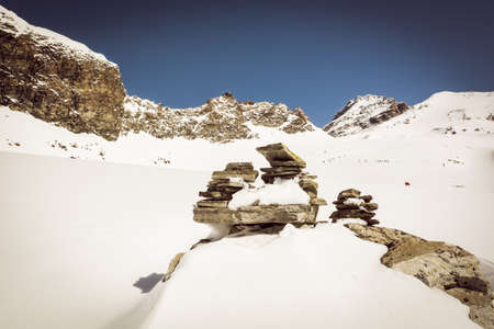 Pyramid build out of stones on snowy mountain slope photo