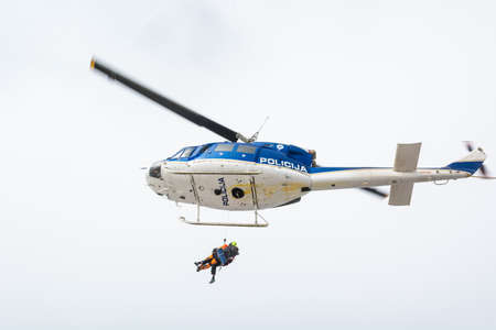 heli: Rescuer and victim ascending into rescue helicopter