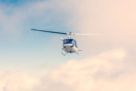 Mountain rescue helicopter flying above clouds 版權商用圖片 - 32623458