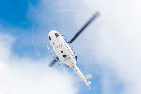 rescue helicopter: Helicopter flying under sky covered with clouds