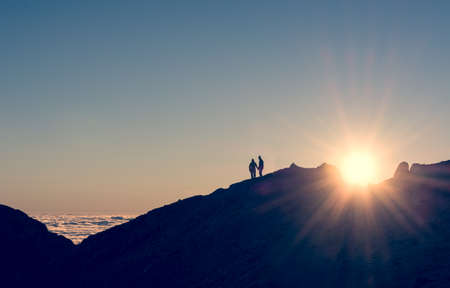 silhouette of a couple holding hands on a mountain ridge with sun rising Stock Photo