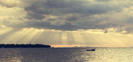 Boat floating on water. Spectacular sun rays shining from the clouds. photo