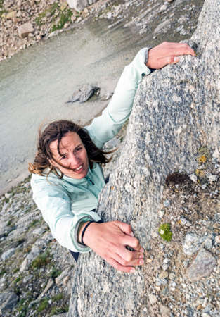 Female climber desperately griping a hold above a lake. Stock Photo