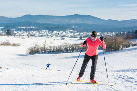 Woman cross country skiing. Ascending a slope with another skier following.