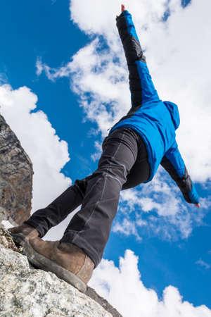 endeavor: Female climber catching balance on mountain ridge.