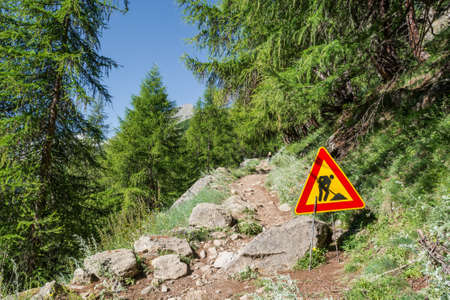 roadwork: Road work sign on a path ascending into a forest.