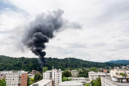 rising dead: Smoke rising near residential buildings. Forest fire.