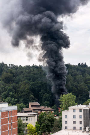 rising dead: Column of black smoke rising near residential buildings. Forest fire. Stock Photo