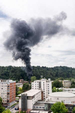 rising dead: Column of black smoke rising above a forest nearresidential area.