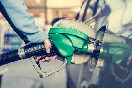 tanque de combustible: Gas de bombeo en la gasolinera. Cerca de una boquilla de combustible de la mano. Foto de archivo