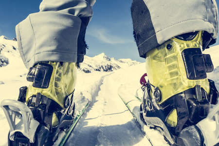 unusual angle: Close up of skiers boots and skies from unusual angle. Mountain peak in the background.