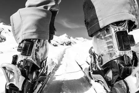 black ski pants: Close up of skiers boots and skies from unusual angle. Mountain peak in the background.