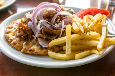 speciality: Plate of Greek lamb gyros with fries and onions. Greek speciality.