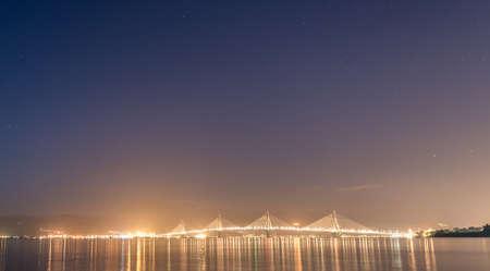 Bridge across the water at dusk. Stars glowing in the sky. Patras, Greece.