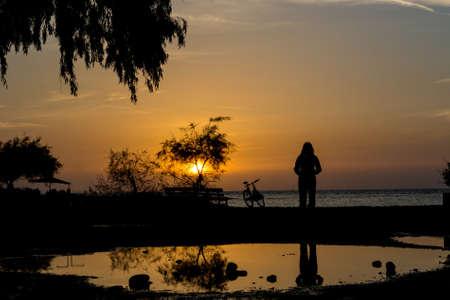 Silhouette einer Person, die auf Strand in der Abenddämmerung. Spiegelbild im Wasser. Standard-Bild