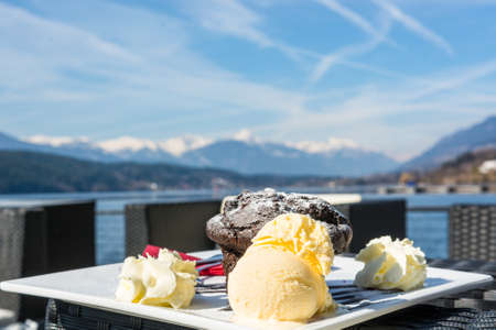 hotel bar: Delicious desert. Chocolote muffin with ice cream at a bar surrounded by mountains. Stock Photo