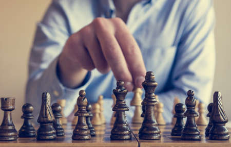 first move: Game of chess. Man making a first move.