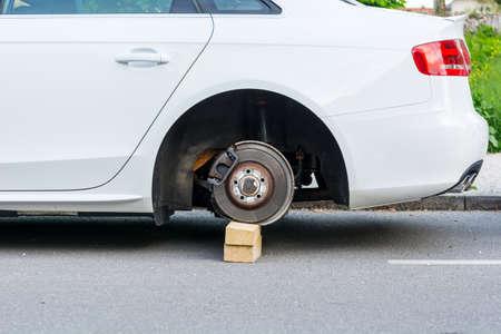 stolen: Car with stolen wheels. White vehicle left on wooden bricks.