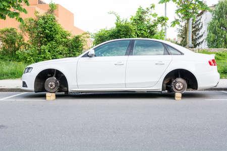 Coche con ruedas robadas. Vehículo Blanca dejó en ladrillos de madera. Foto de archivo