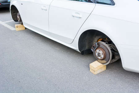 alloys: Car with stolen wheels. White vehicle left on wooden bricks.