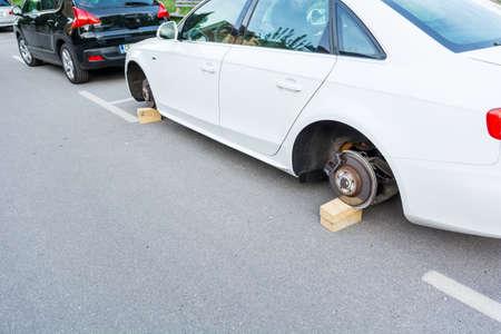 Car with stolen wheels. White vehicle left on wooden bricks.