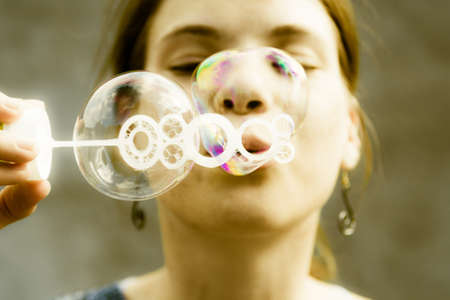 preety: Young girl having fun and blowing bubble in the shape of a hearth. Stock Photo