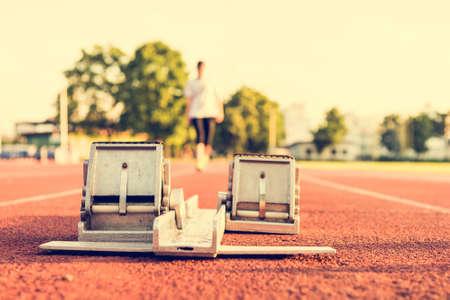 Closeup of a starting block. Sprinter in distance. photo