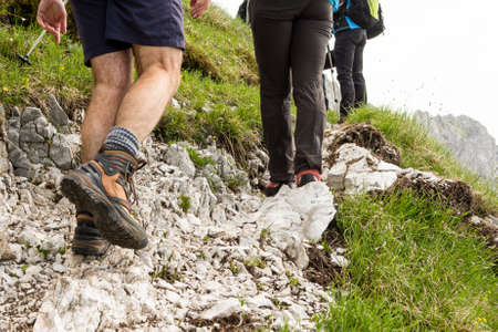 Closeup of trekking shoes. Hikers ascending a rocky road. Stock Photo