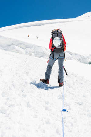 ice axe: Female mountaineer ascending a glacier. Alpinst holding ice axe. Stock Photo