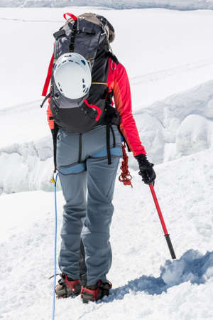 crampons: Female mountaineer ascending a glacier. Alpinst holding ice axe. Stock Photo