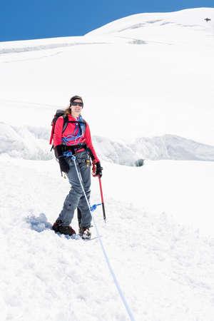 alpinist: Female alpinist standing on glacier. Woman wearing mountaineering gear.