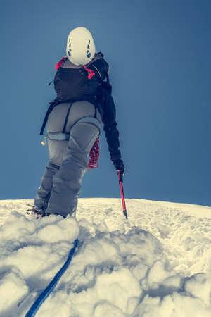 ascending: Female climber ascending a glacier. Shot from underneath.