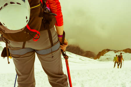 alpinist: Alpinist looking down the slope. Close up of a mountaineer.