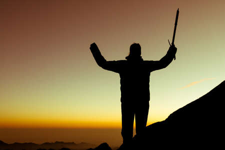 alpinist: Silhouette of alpinist celebrating. Person holding ice axe at sunrise. Stock Photo