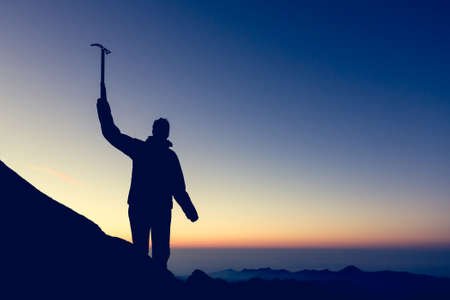 ice axe: Silhouette of alpinist celebrating. Person holding ice axe at sunrise. Stock Photo