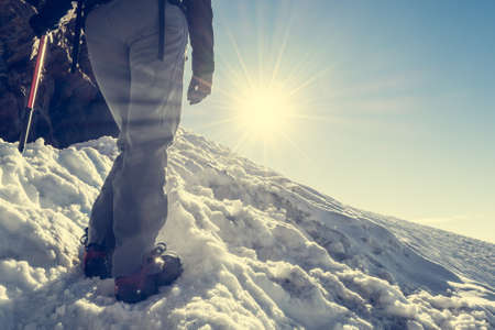 crampons: Close up of hiking shoes with crampons. Alpinist ascending a snowy mountain.