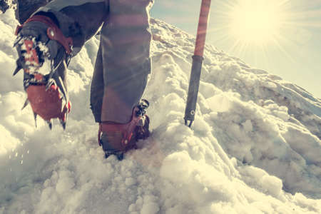 ice axe: Close up of hiking shoes with crampons. Alpinist ascending a snowy mountain.