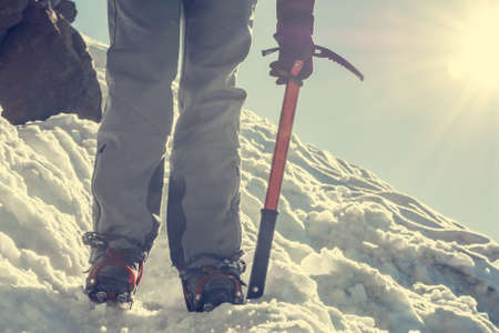 crampons: Close up of hiking shoes with crampons and ice axe. Alpinist descending a snowy slope.