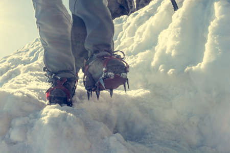 ice axe: Close up of hiking shoes with crampons and ice axe. Alpinist descending a snowy slope.