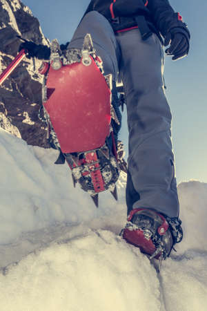 crampons: Close up of hiking shoes with crampons and ice axe. Alpinist while stepping down.