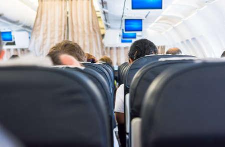 interior shot: Airplane interior. Shot between seats at female passanger. Stock Photo