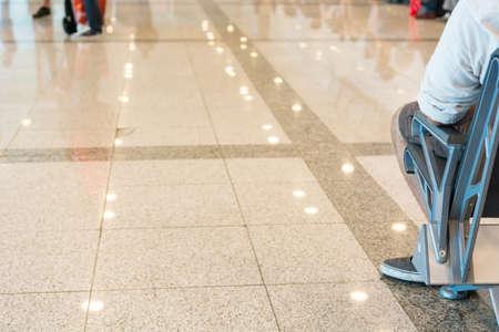 persona seduta: L'aeroporto sala d'attesa. Primo piano di persona che si siede su una panchina. Archivio Fotografico