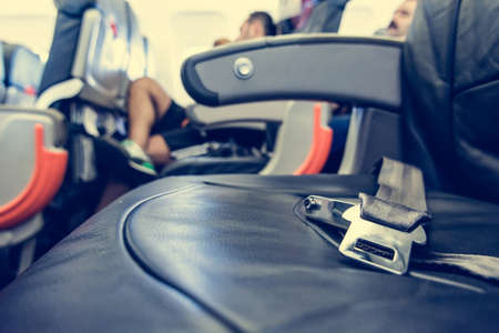 safety belt: Airplane interior. Close up of safety belt on seat.