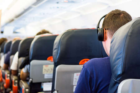 Airplane interior. Passanger listening to the music. Stock Photo