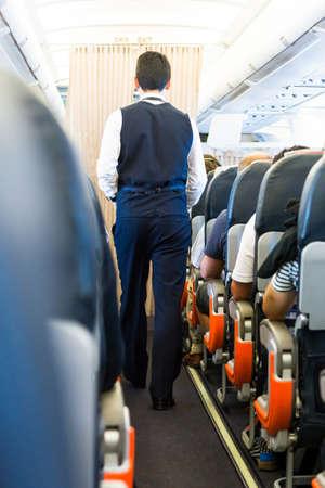 personel: Airplane interior. Cabin crew walking down the aisle.