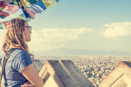 city of sunrise: Young woman enjoying the evening view of a city. Kathmandu.