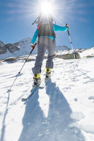 touring: Skier ascending a slope. Ski touring where skier is tackling a steep slope.