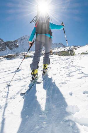 ascending: Skier ascending a slope. Ski touring where skier is tackling a steep slope.