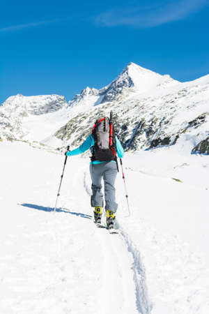 ascending: Ski touring in sunny weather. Female skier ascending a trail.
